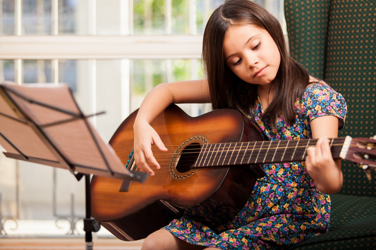 child learning to play guitar chords