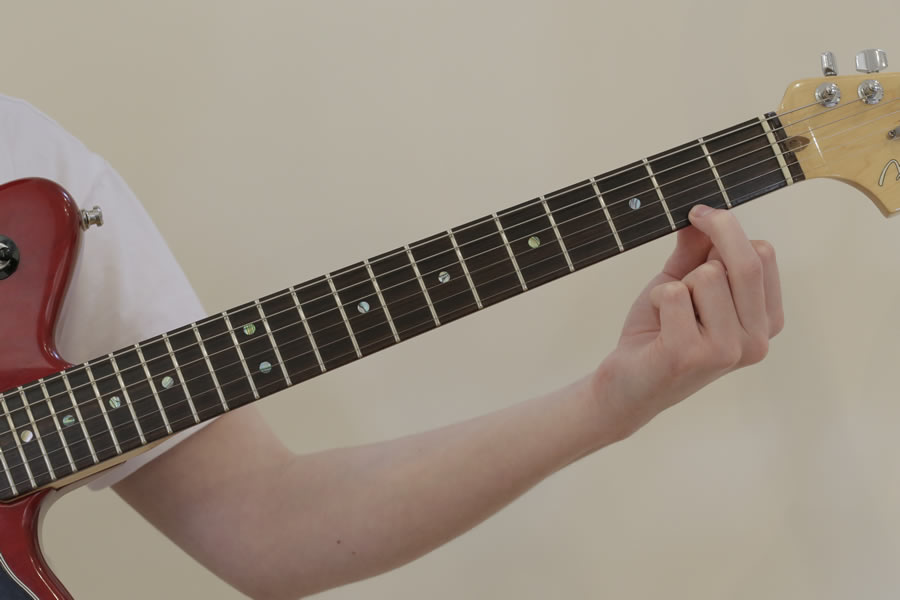 man placing finger on guitar neck to play guitar scale
